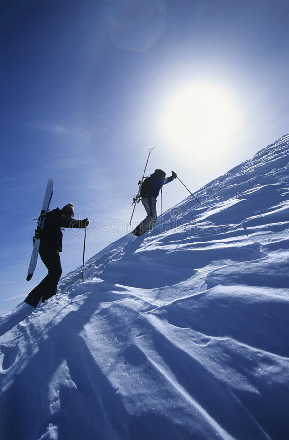 Skiers Hiking To Mountain Summit. Side view of skiers hiking to mountain summit royalty free stock images