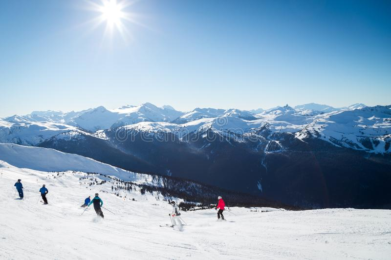 Skiers on a hill at the top of Blackcomb, 7th Heaven, with a view looking toward Whistler on a sunny day. stock image