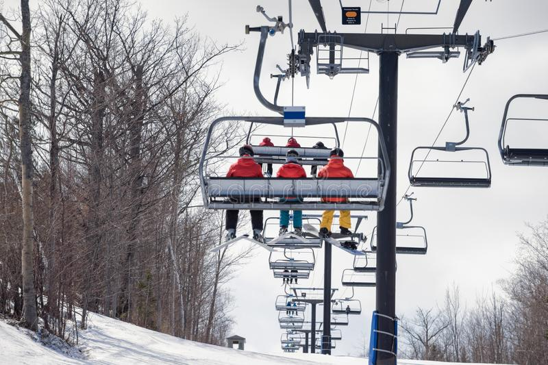 Skiers ride up the hill on a chairlift stock photography