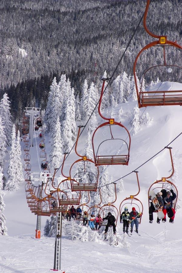 Skiers riding the ski-lift royalty free stock image