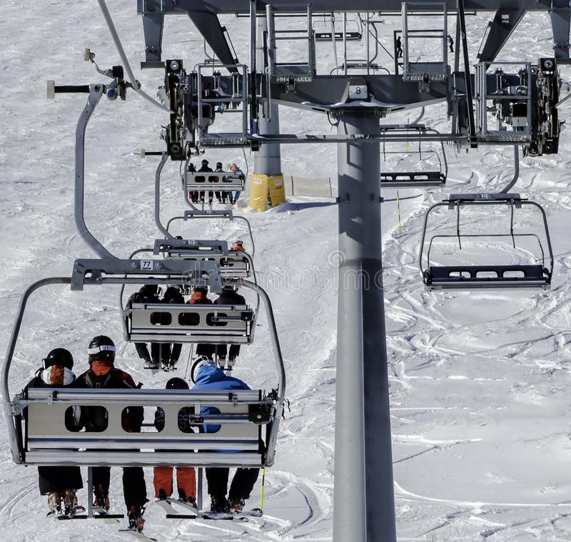 Skiers on a ski lift stock image
