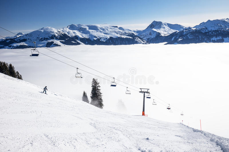 Skiers on ski lift enjoying the view to foggy Alps in Austria and beautiful snowy country panorama in famous Kitzbuehel mountain royalty free stock photo