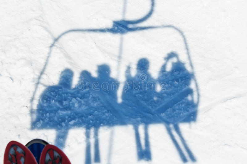 Skiers on a ski lift. Shadow of skiers on a ski lift at winter mountain resort stock image