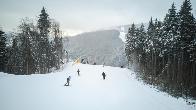 Skiers and snowboarders go down the slope in a ski resort Bukovel, Ukraine royalty free stock photos
