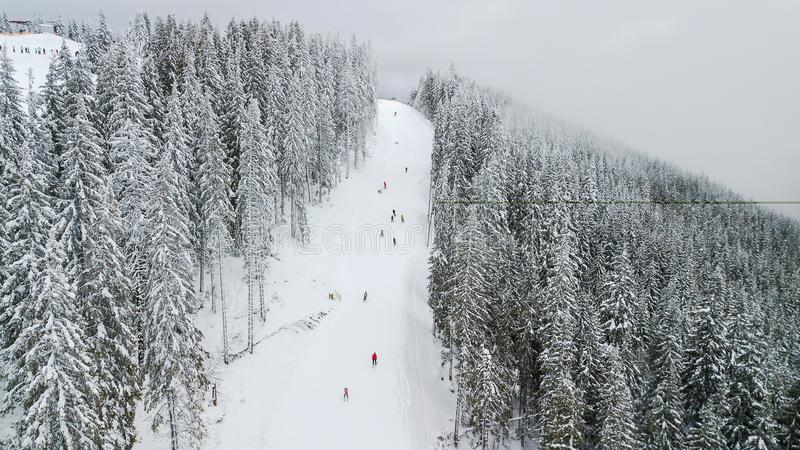 Skiers and snowboarders go down the slope in a ski resort Bukovel, Ukraine stock photography