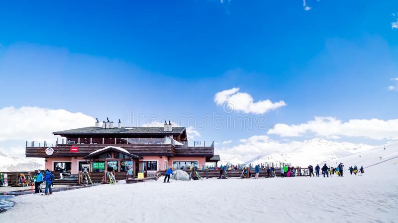 Skiers, snowboarders relaxing near mountain hut, Alps, Livigno, Italy. Livigno, Italy, April 2016 Skiers, snowboarders relaxing near mountain hut, winter ski and royalty free stock photos