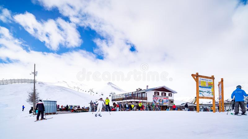 Skiers, snowboarders relaxing near mountain hut, Alps, Livigno, Italy. Livigno, Italy, April 2016 Skiers, snowboarders relaxing near mountain hut, winter ski and stock image