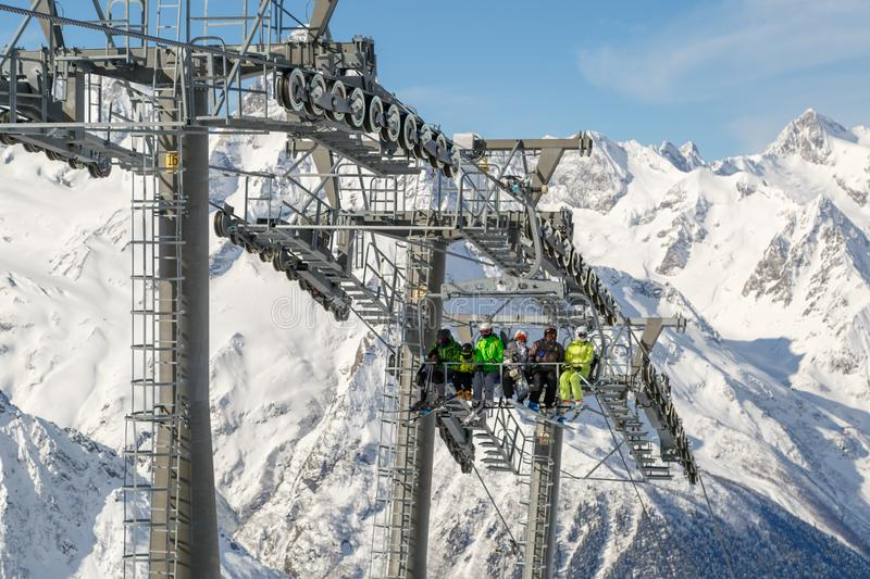 Skiers and snowboarders rise on a modern cable lift to a high mountain stock photo
