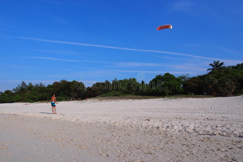 Skies Of Cuba With Kite Flier. Condensation trails from airplanes and man flying a kite beach at Varadero Cuba stock images