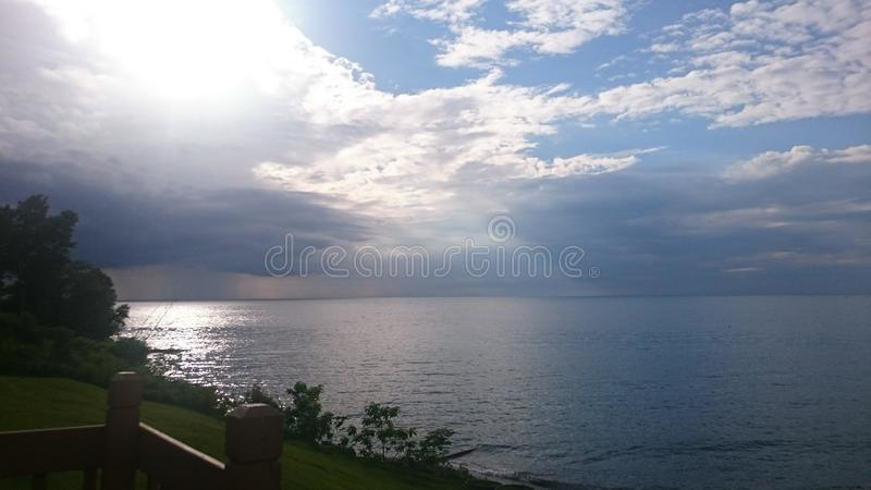 Skies after rain. Sun behind the rainy skies above the lake Erie in Ohio, USA royalty free stock image