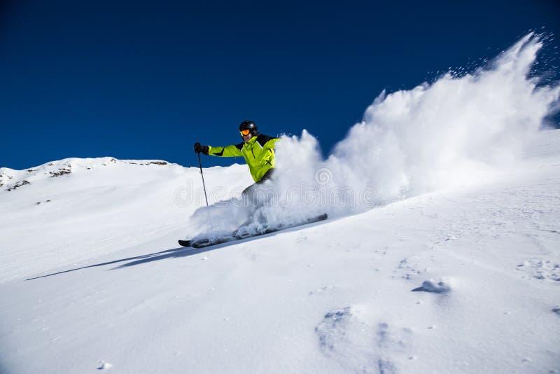 Skieur alpin sur la piste, skiant en descendant photo libre de droits