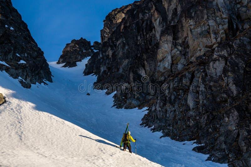Skieur augmentant ou bootpacking un couloir ou un descendeur raide entre deux falaises de roche dans le backcountry des montagnes photo stock