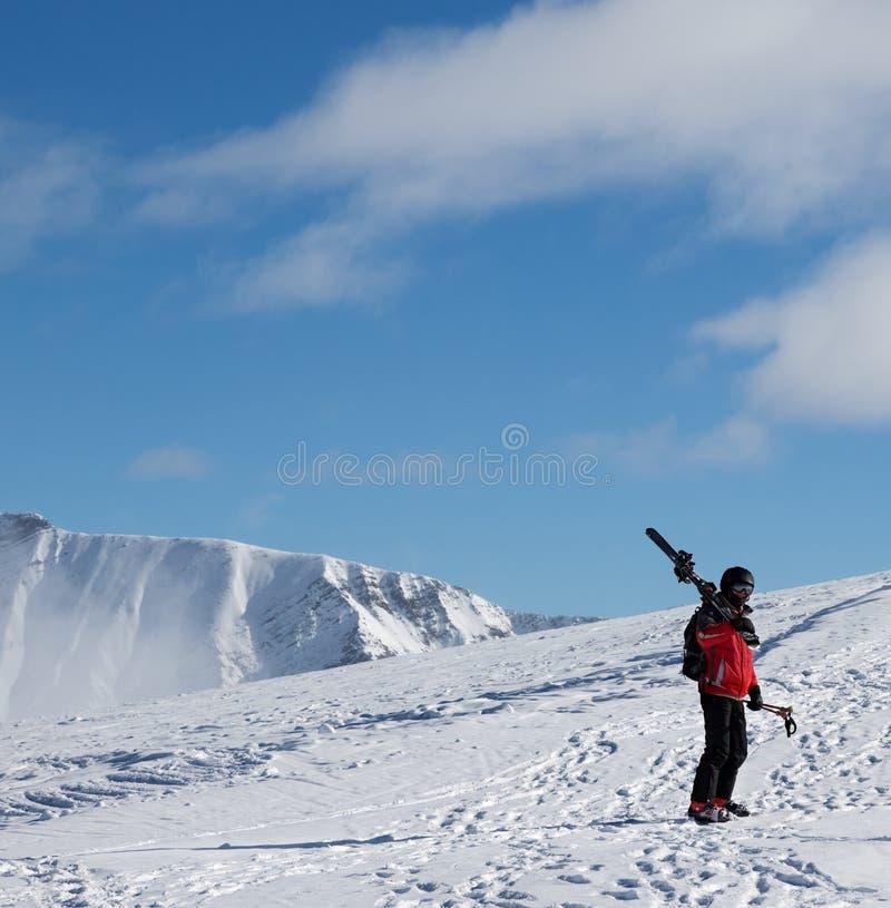 Skieur avec des skis sur son épaule dans le beau jour du soleil Montagnes de Caucase en hiver, la Géorgie, région Gudauri photo libre de droits