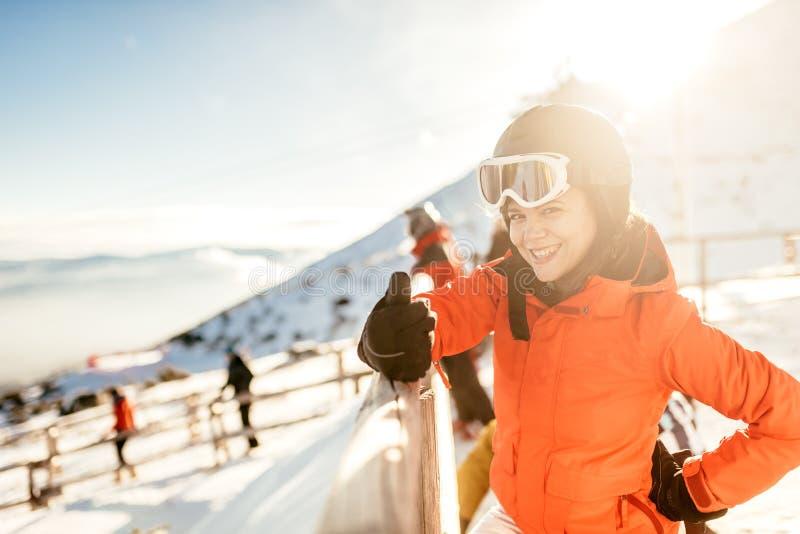 Skieur de jeune femme sur des pentes Portrait de jeune femme souriant dans l'équipement de ski, les lunettes de port et le casque photos stock