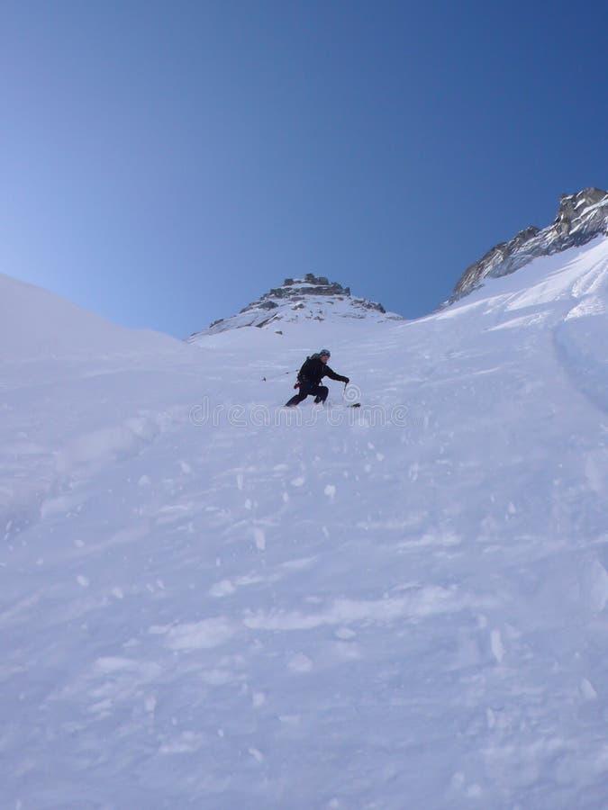 Skieur extrême skiant une descente du nord très raide de ski de visage dans les Alpes de la Suisse photos stock