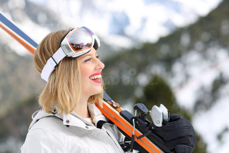 Skieur heureux tenant des skis regardant la montagne photo stock