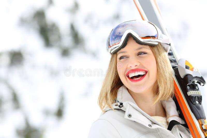Skieur heureux tenant des skis regardant le côté images stock