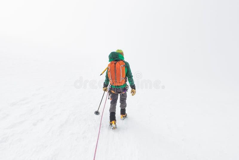 Skieur marchant vers le haut d'une pente neigeuse raide dans les montagnes photos stock