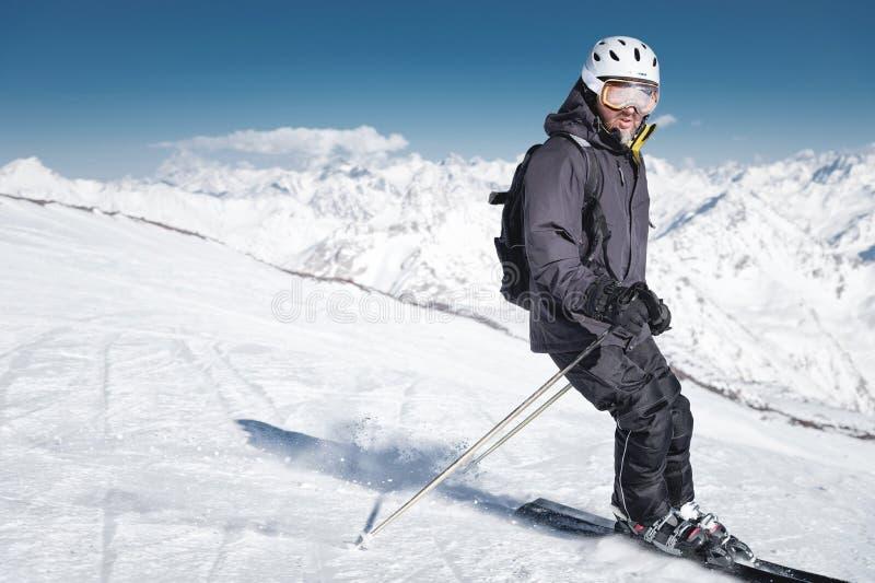 Skieur masculin barbu dans un casque et freins d'un masque de ski avec la poudre de neige sur des skis dans la perspective de cou photos libres de droits