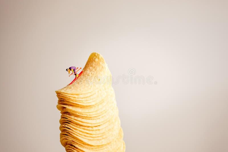 Skieur miniature glissant en bas de la pile de pommes chips photo libre de droits