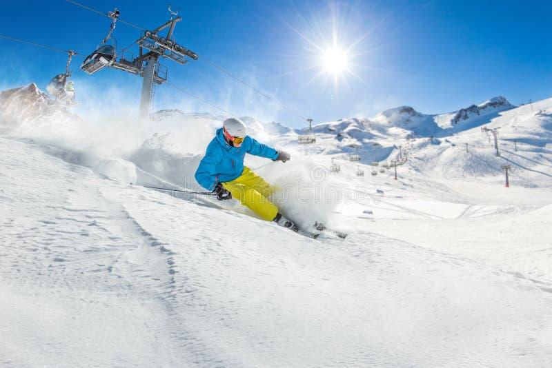 Skieur skiant en descendant en hautes montagnes photo stock