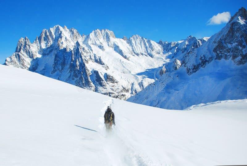Skieur skiant en descendant en hautes montagnes contre le soleil photographie stock libre de droits