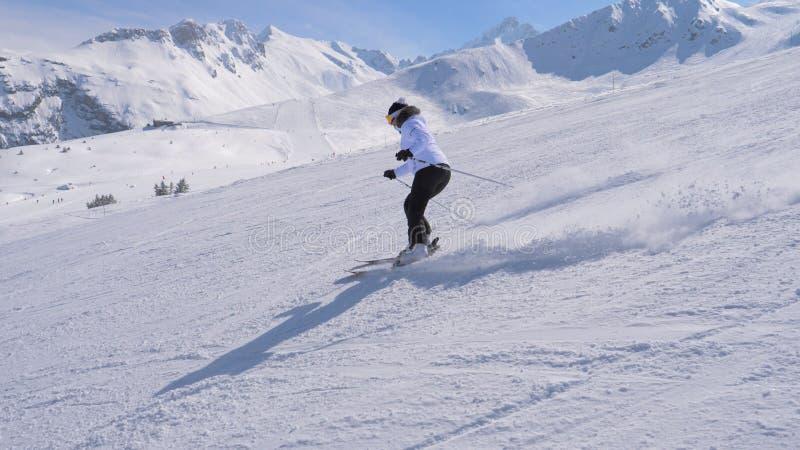 Skieur sportif de femme découpant professionnellement en bas de la pente dans les montagnes images stock
