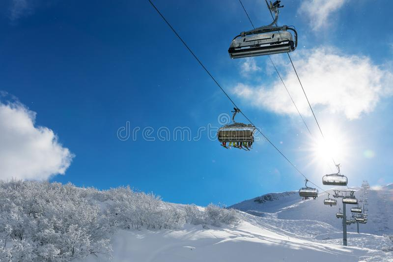 Skieurs dans un remonte-pente en montagnes neigeuses photo stock