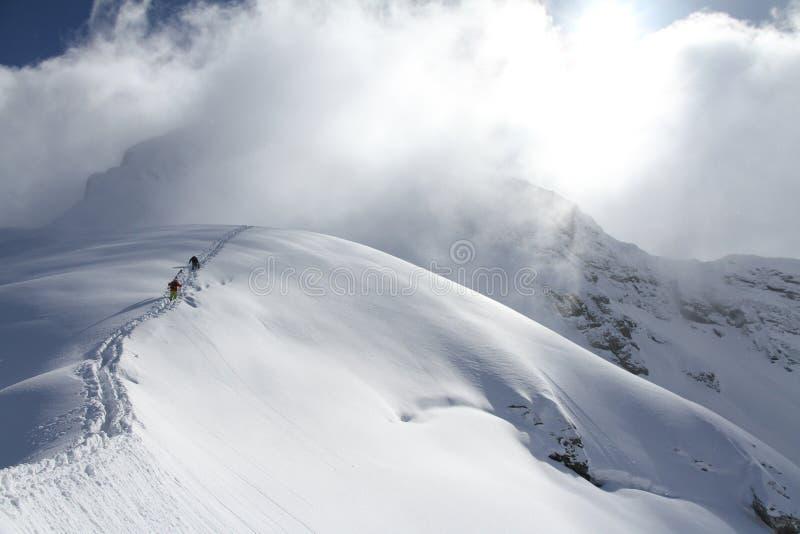 Skieurs escaladant une montagne neigeuse image stock