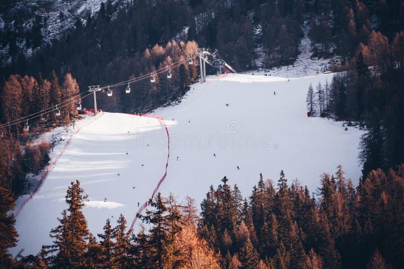 Skieurs et chaise de remonte-pente avec la vue des montagnes neigeuses d'Alpes photo stock