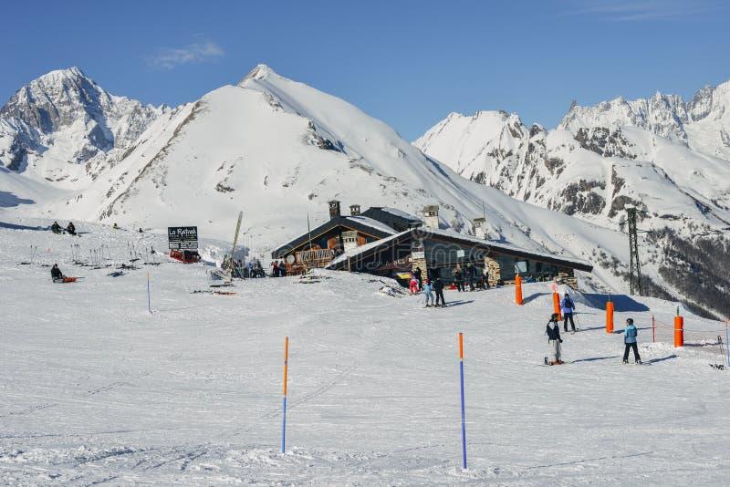 Skieurs et surfeurs à côté d'une carlingue en bois dans les Alpes italiens pendant l'hiver, avec l'espace de copie image stock