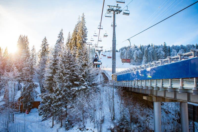Skieurs sur le remonte-pente montant à la station de sports d'hiver avec le beau fond des forêts photos libres de droits
