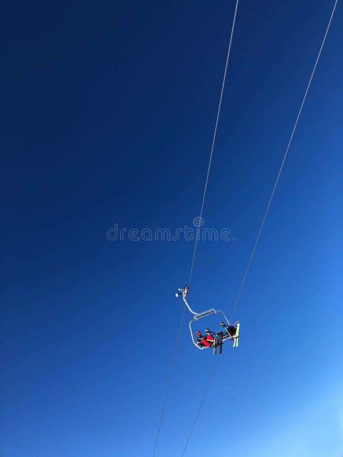 Skieurs sur Ski Chair Lift In une station de vacances avec le ciel bleu photographie stock