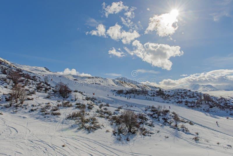 Skieurs sur une piste dans la station de sports d'hiver alpine images libres de droits