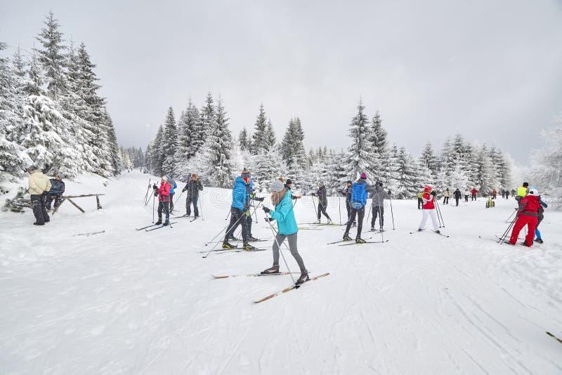 Skieurs transnationaux se reposant sur l'intersection de traînées image stock