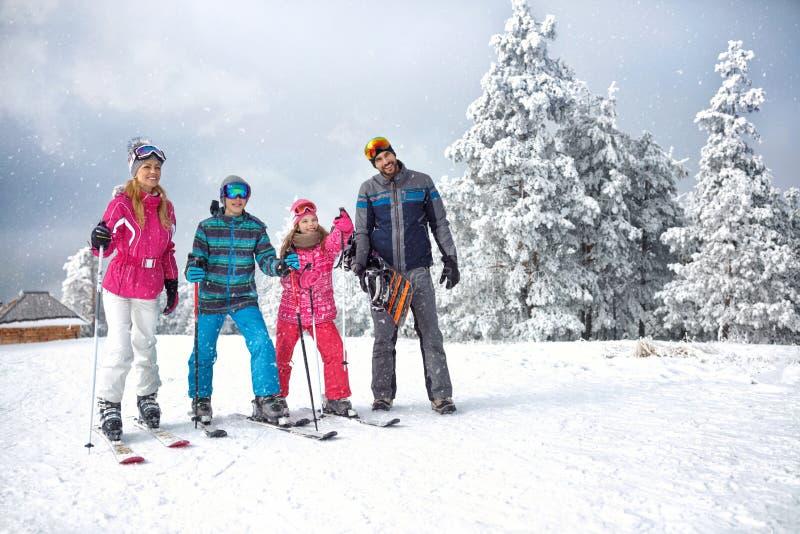 Skifahrenfamilie, die Winterferien auf Schnee am sonnigen kalten Tag genießt stockfotografie