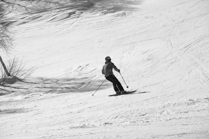 Skifahrer absch?ssig auf schneebedeckter Skisteigung am sonnigen Tag lizenzfreies stockbild