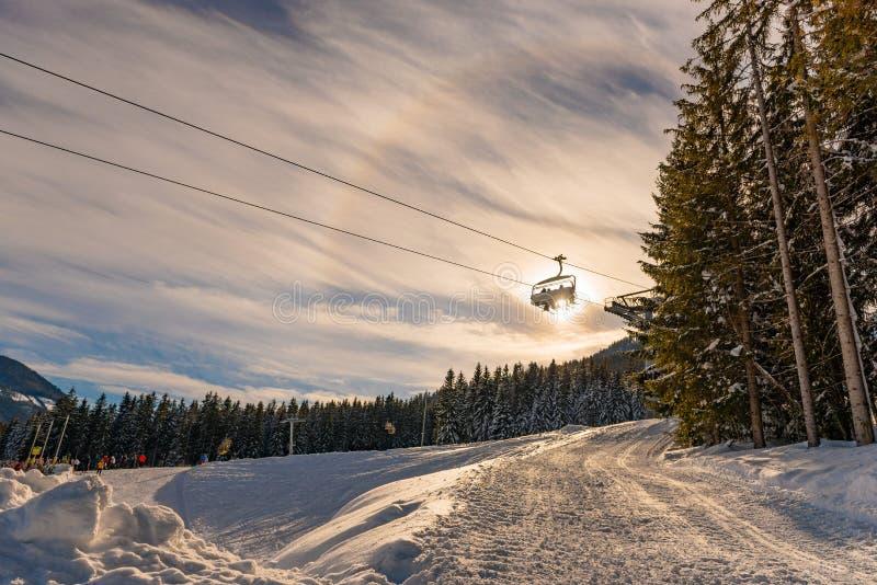Skifahrer auf dem Skisessellift auf dem Hintergrund der Sonne und des blauen Himmels stockfotos