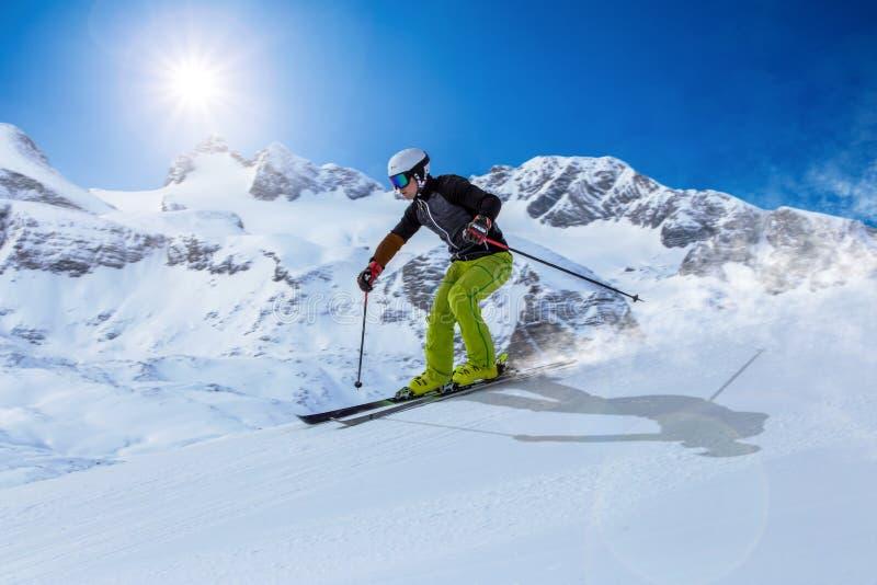 Skifahrer, der abwärts während des sonnigen Tages im Hochgebirge in Dachstein-Bereich, Österreich Ski fährt lizenzfreie stockfotografie
