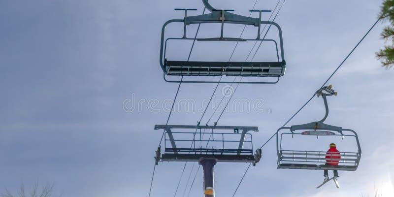Skifahrer, der allein auf einen Skiaufzug in Park City Utah fährt lizenzfreie stockbilder