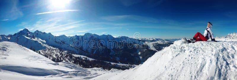 Skifahrer, der auf einen Berg sitzt stockfotografie