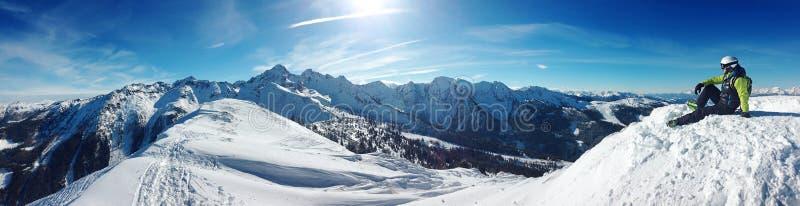 Skifahrer, der auf einen Berg sitzt lizenzfreies stockfoto