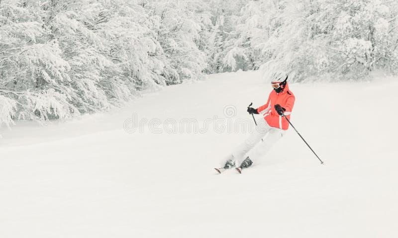 Skifahrer der jungen Frau, der abwärts auf Ski Piste läuft lizenzfreies stockbild