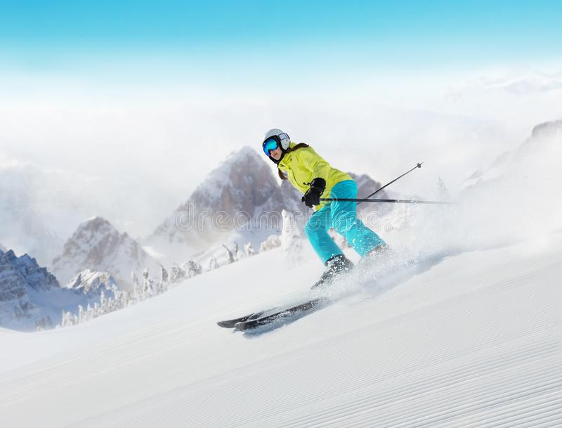 Skifahrer der jungen Frau, der hinunter die Steigung in den alpinen Bergen läuft stockfotos