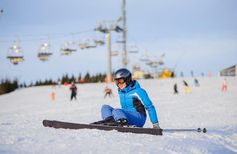 Skifahrer der jungen Frau nach dem Fall auf Berghang lizenzfreies stockbild
