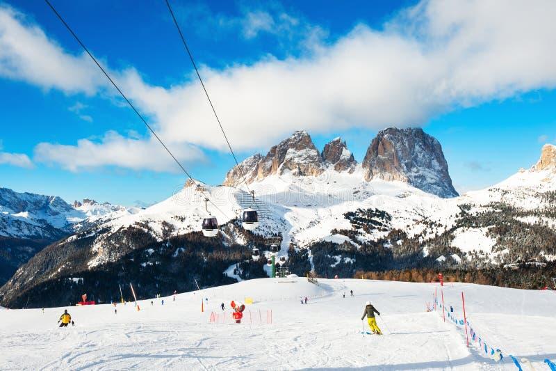 Skifahrer, die hinunter die Steigung im Skiort in Winter Dolomit Ski fahren Val di Fassa, Italien stockbild