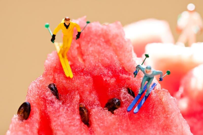 Skifahrer, die von den Wassermelonenbergen schieben Kreatives Sommerfestkonzept Winterlebensstil, Sporttätigkeits-Extrembild stockfotos