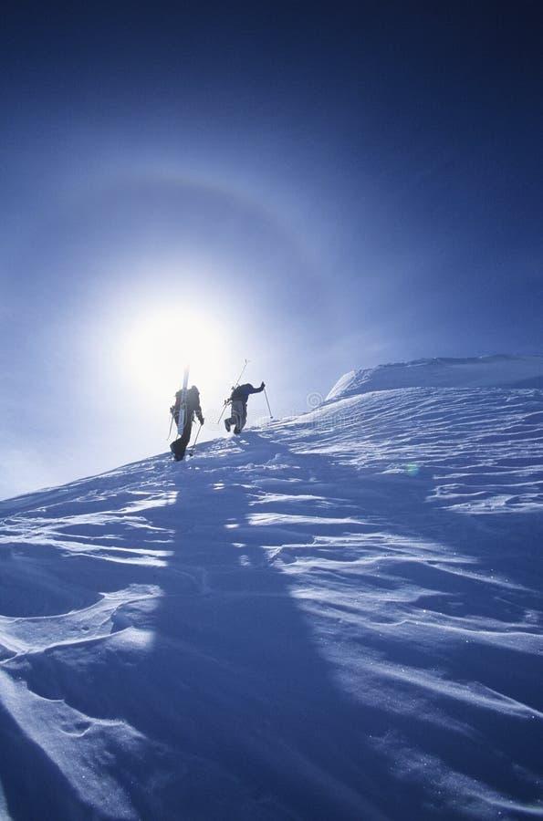 Skifahrer, die zum Gebirgsgipfel wandern stockfotos