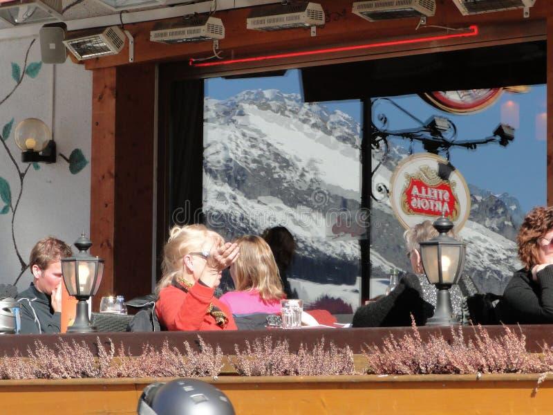 Skifahrer entspannen sich in einer Bistro im Freien lizenzfreies stockbild