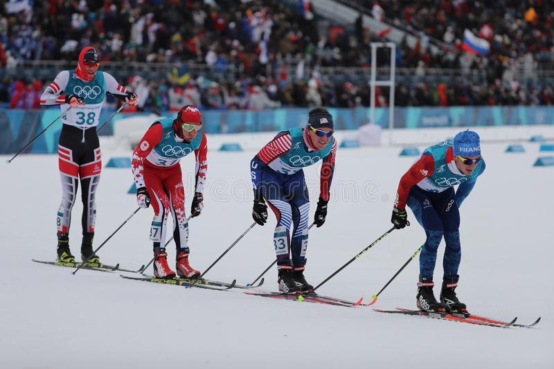 Skifahrer konkurrieren beim Massenanfang im Männer ` s 15km + 15km Skiathlon an der 2018 Winterolympiade lizenzfreie stockfotos